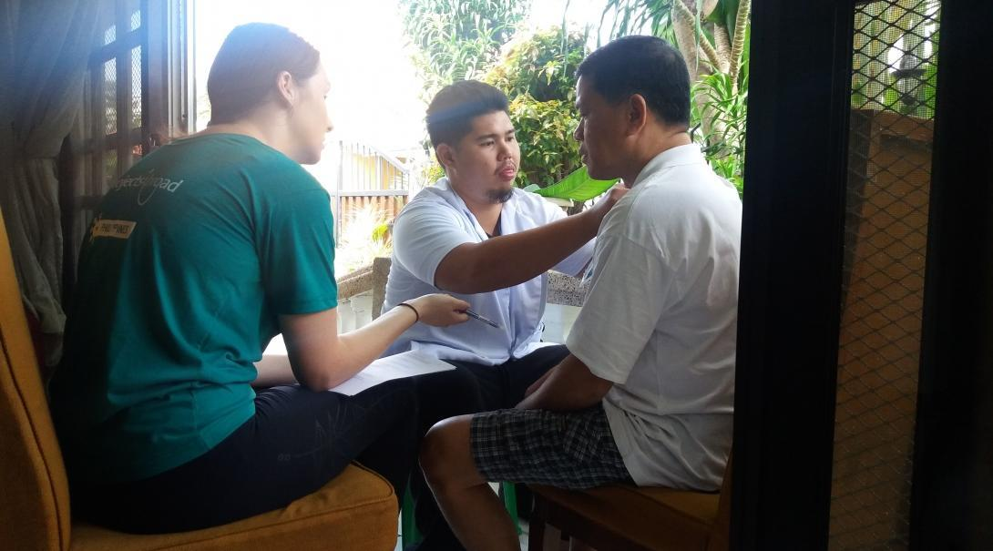 Interns are pictured helping a man exercise his shoulder whilst they complete their occupational therapy internship in the Philippines.